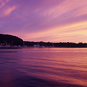 The setting sun casts a purple color in the sky, clouds, and lake in Peninsula State Park, near Egg Harbor, Wisconsin.  Door County on the Door Peninsula in Wisconsin is a popular vacation location in the Midwest.  The Peninsula is south of the Upper Peninsula of Michigan.  It offers a great place to relax and enjoy nature. Door County has five state parks, ten lighthouses, and beautiful sandy beaches with the fresh, clear water of Lake Michigan.