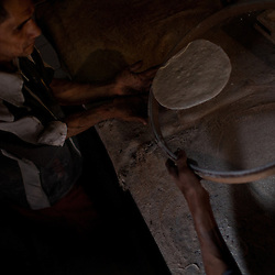 From left, Abdi Maghi and Zamir move the flattened dough into an oven.