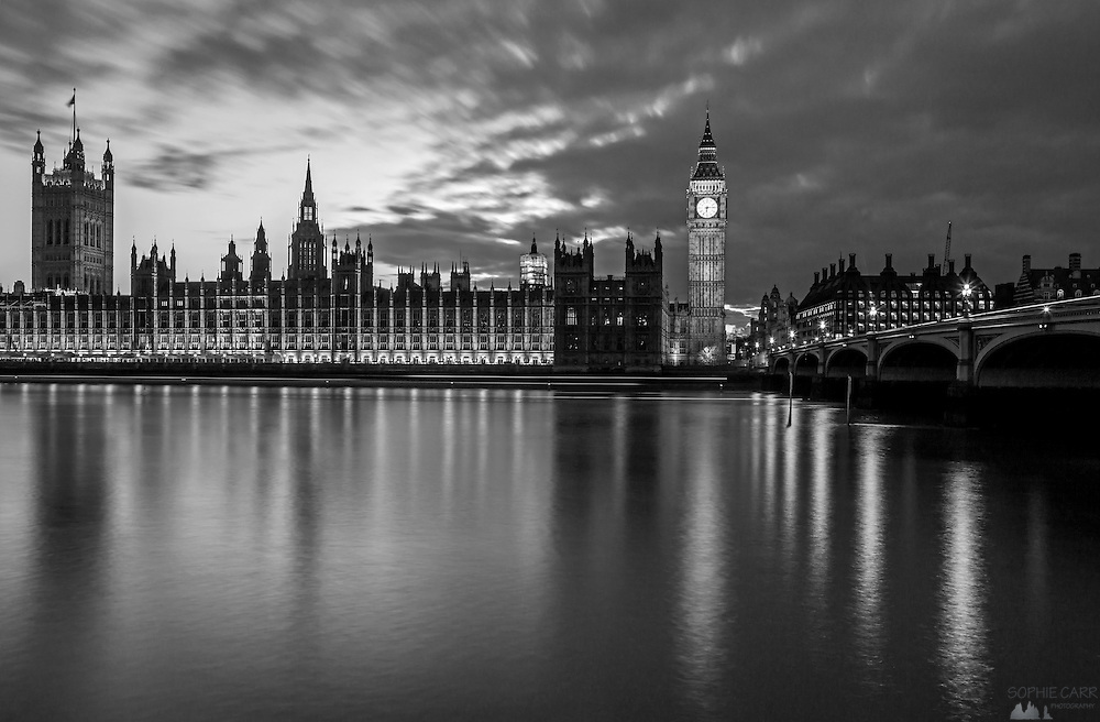Black & white long-exposure shot of the Houses of Parliament and Westminster Bridge in central London, just after sunset.