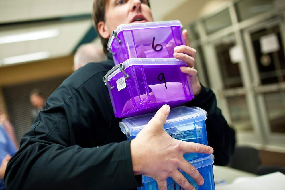 John Kallen collects ballot boxes at a caucus site at Summit Middle School on Tuesday, January 3, 2012 in Johnston, IA.