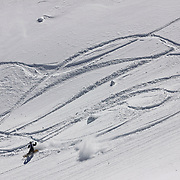 SHOT 3/12/10 11:23:50 AM - A snowboarder makes tracks through fresh powder in an open bowl at Silverton Mountain. Skiing and snowboarding at Silverton Mountain in Silverton, Co. Silverton Mountain is unique amongst ski resorts requiring a guide (most of the season), avalanche gear and limiting the number of daily visitors. There are multiple bowls, chutes, cliffs and natural terrain features to be discovered during a visit to Silverton Mountain. It is the highest Ski Area in North America with a peak of 13,487' and it is also the steepest with no easy way down. The mountain is left in it's natural state with the exception of the avalanche reduction work which occurs. There is only one chair at the mountain though most skiiers and snowboarders will end up hiking in various directions at the top. The mountain also features heliskiing trips for $159 a trip (at the time of visit). The mountain opened in 2002. (Photo by Marc Piscotty / © 2010)