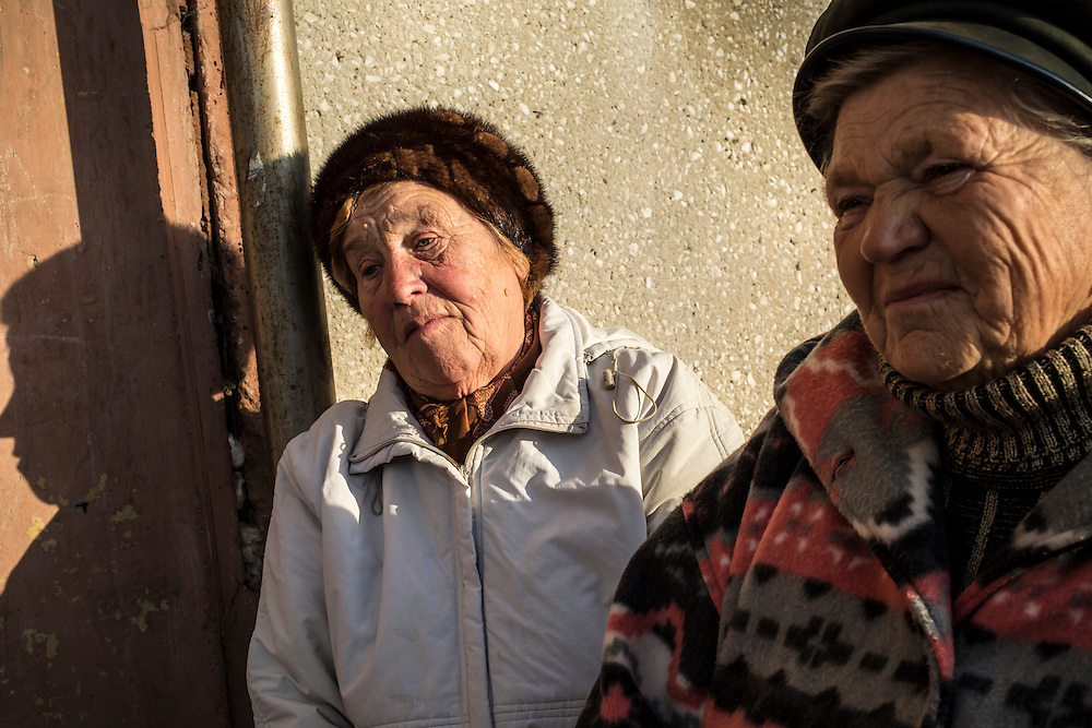 Two women sit outside their apartment building on Thursday, October 24, 2013 in Baikalsk, Russia.