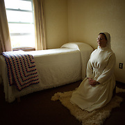 """Sister Michele Armstrong prays in her """"cell"""" at Our Lady of the Mississippi Abbey, a monastery of Trappist nuns.  Armstrong, a novice at the convent, spends time each day in private prayer and communion with God.  The community of 22 Roman Catholic women follow Jesus Christ through a life of prayer, silence, simplicity and ordinary work.  Their home is a beautiful monastery which sits high on a bluff, overlooking the Mississippi River."""
