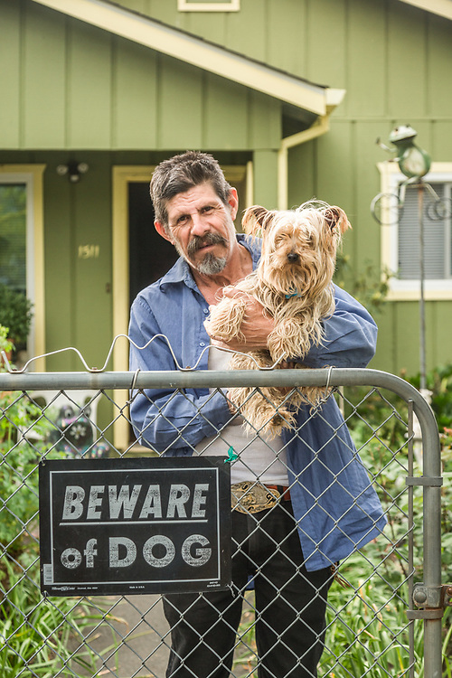 Professional gardener and 40 year resident of Calistoga, Lorenzo Perez stands at his front gate with his guard dog, Gramon.