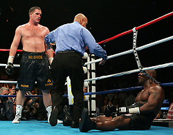 Kevin McBride looks down at a fallen Mike Tyson during the 6th round of their fight at the MCI Center in Washington, DC.  McBride won the fight when Tyson failed to answer the bell for the 7th round.