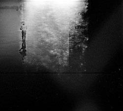 Outdated film picture of a fisherman standing in West Lake shallow waters, Hanoi, Vietnam, Southeast Asia