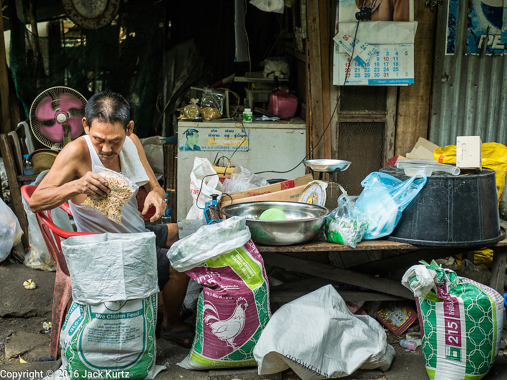 07 APRIL 2016 - BANGKOK, THAILAND: A man prepares bird seed for sale in Mahakan Fort.  The community is known for fireworks, fighting cocks and bird cages. Mahakan Fort was built in 1783 during the reign of Siamese King Rama I. It was one of 14 fortresses designed to protect Bangkok from foreign invaders, and only of two remaining, the others have been torn down. A community developed in the fort when people started building houses and moving into it during the reign of King Rama V (1868-1910). The land was expropriated by Bangkok city government in 1992, but the people living in the fort refused to move. In 2004 courts ruled against the residents and said the city could take the land. The final eviction notices were posted last week and the residents given until April 30 to move out. After that their homes, some of which are nearly 200 years old, will be destroyed.       PHOTO BY JACK KURTZ