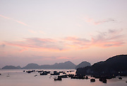 Panorama of limestone karsts and fishing boats at Cat Ba harbour at sunset, Cat Ba Island, Vietnam