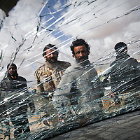 Rebel fighters are seen through the window of a car that was destroyed during clashes with government troops outside of Ajdabiya, 100 miles south of Benghazi, Libya. March 2011.
