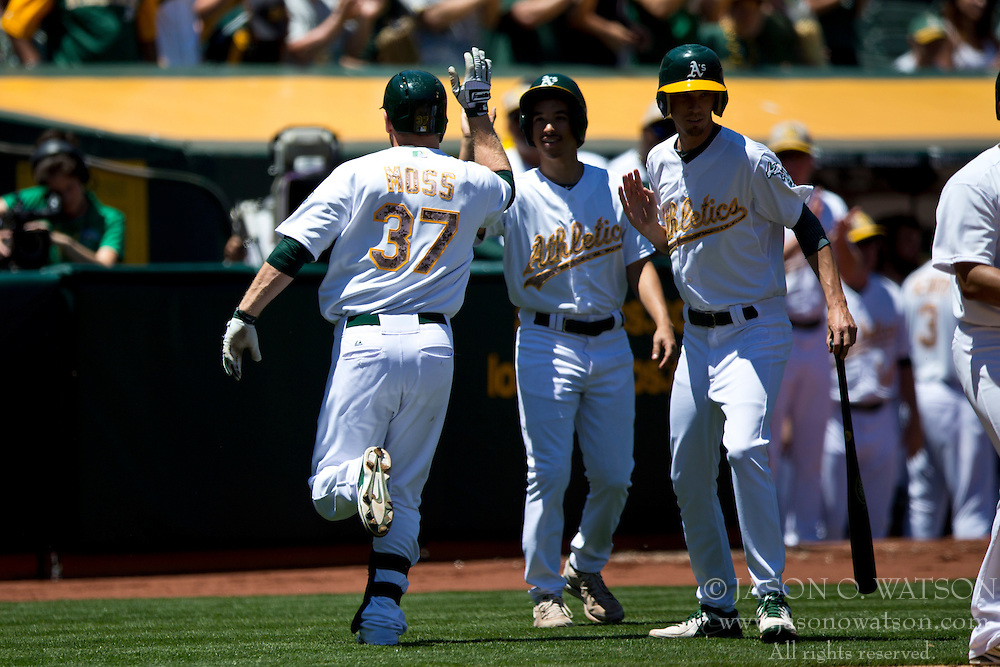 OAKLAND, CA - MAY 26:  Brandon Moss #37 of the Oakland Athletics is congratulated by teammates after hitting a home run off of Drew Smyly #33 of the Detroit Tigers (not pictured) during the second inning at O.co Coliseum on May 26, 2014 in Oakland, California. The Oakland Athletics defeated the Detroit Tigers 10-0.  (Photo by Jason O. Watson/Getty Images) *** Local Caption *** Brandon Moss