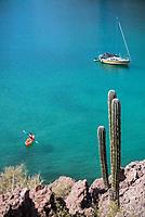 Kayaker, sailboat and cardon at Puerto Agua Verde in Baja California Sur, Mexico.