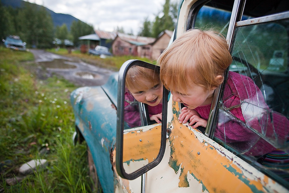 A young girl plays in one of the many old abandoned trucks scattered around the town of McCarthy, Alaska.