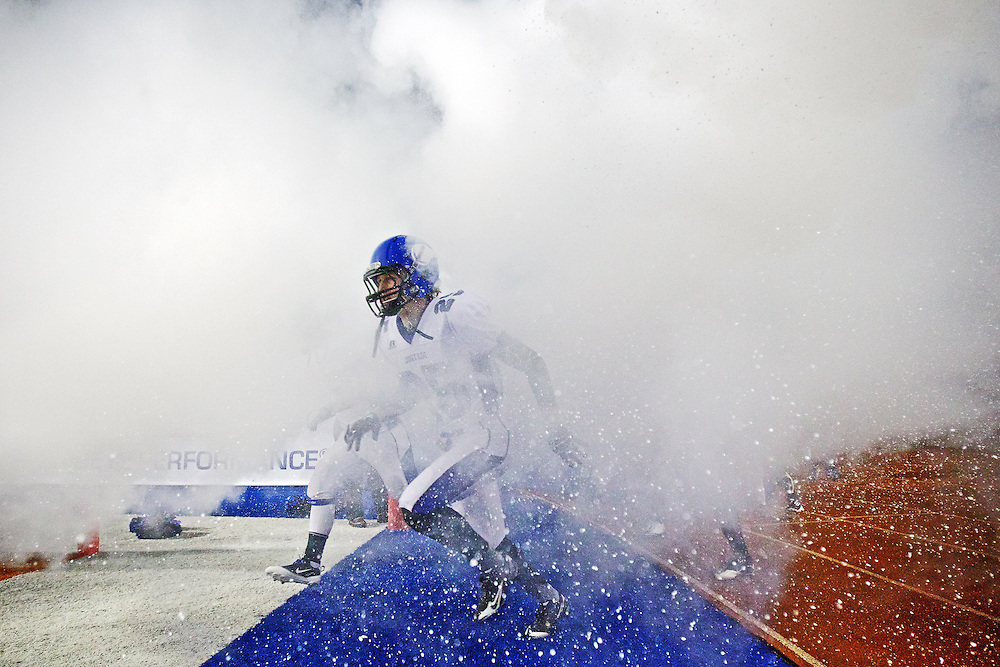Coeur d'Alene High's Cody Schneider races through the fog created by fire extinguishers shot off to mark the Viking's entrance into the 5A State Championship football game Friday against Eagle High at Bronco Stadium in Boise.