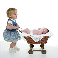 21 July 2008: Two year old toddler Lucy Berg girl pushing newborn sister in a baby carriage on a white background in studio.