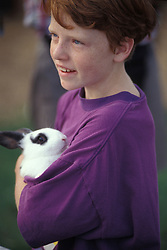 Young child plays with pet rabbit at family style vacation campground.
