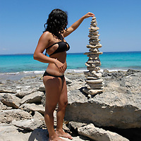 MR Young brunette woman doing a stone sculpture in Formentera
