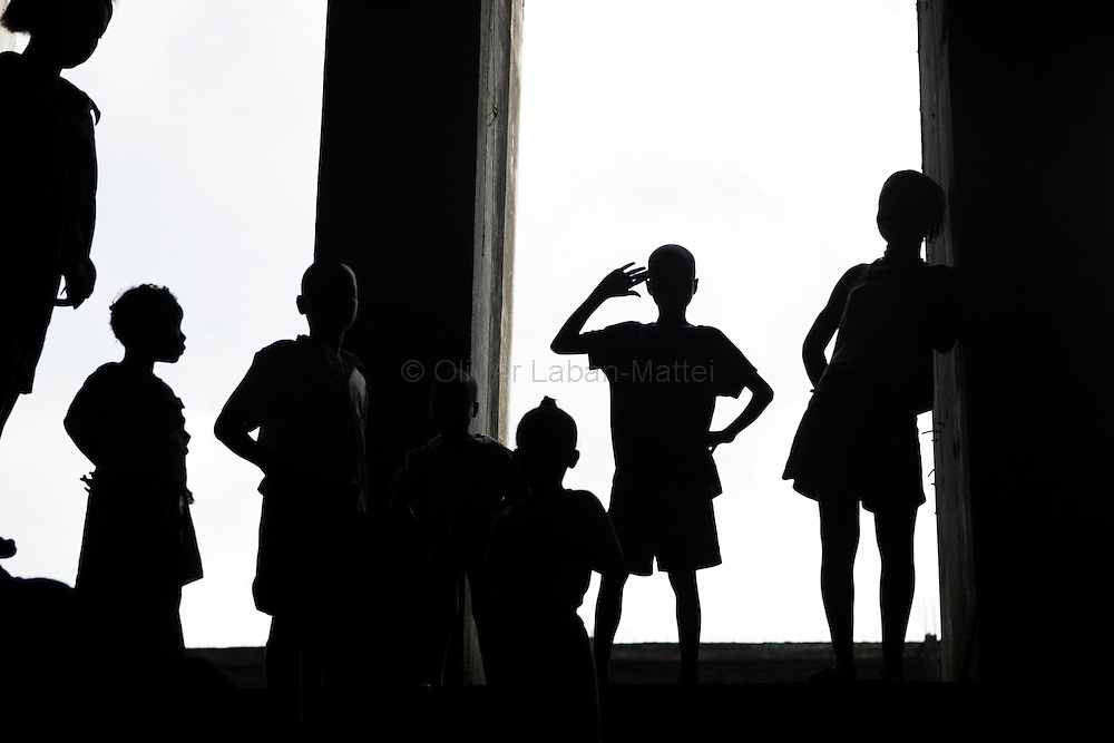 "Photo taken 19 September 2005 of children in a doorway at the former uncompleted Ministry of National Defense building in Congo Town on the outskirts of Monrovia. The ""Pentagon"", named this way by its occupants, shelters 394 families totalling approximately 3,000 people who were booted out in May 2005 of the Barclay Training Center, which had been their home for the last two decades. Former soldiers, who fought for former Liberian presidents Samuel Doe and Charles Taylor, live in this building with no water or electricity, overcoming past differences. The construction of the building started in 1984 under Doe's leadership, and the war interrupted the its completion and later served as a base for Taylor's men."
