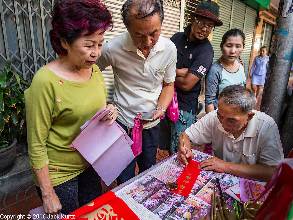 """04 FEBRUARY 2016 - BANGKOK, THAILAND:  People watch a traditional Chinese calligrapher write out New Years greetings in Bangkok's Chinatown district, before the celebration of the Lunar New Year. Chinese New Year, also called Lunar New Year or Tet (in Vietnamese communities) starts Monday February 8. The coming year will be the """"Year of the Monkey."""" Thailand has the largest overseas Chinese population in the world; about 14 percent of Thais are of Chinese ancestry and some Chinese holidays, especially Chinese New Year, are widely celebrated in Thailand.     PHOTO BY JACK KURTZ"""