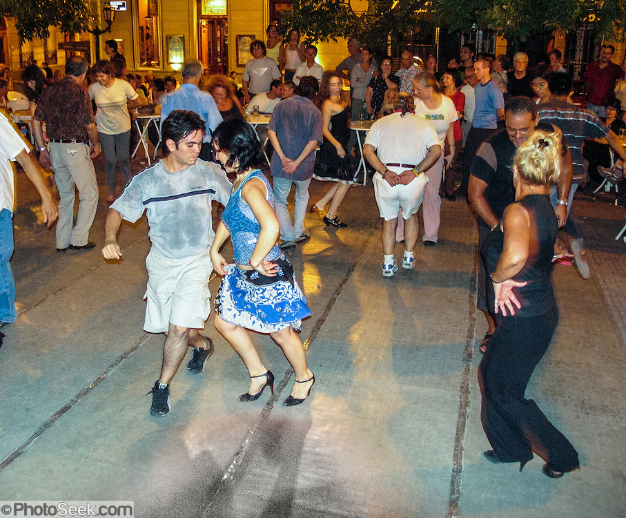 "People dance the Chamamé at a free public dance in Dorrego Square, in San Telmo barrio of Buenos Aires, Argentina, South America. Chamamé is a folk music genre from northeast Argentine (""Litoral,"" including La Mesopotamia, Región Mesopotámica) and southern Brazil. Accordion-based Chamamé arose in Corrientes Province, an area with many immigrants from Poland, Austria, and Germany (many of them Jews), who brought Polkas, Mazurkas and Waltzes which mixed with local Spanish music."