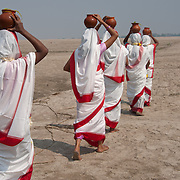 Returning home after performing religious rituals on the bank of river Ganga, held sacred by followers of Hinduism. Millions of Hindus bathe in the river daily if living close, or annually at special holy places (tirthas). Many cast the ashes of their dead into its waters, and cremation temples are found along its banks in many (pilgrimage) places.