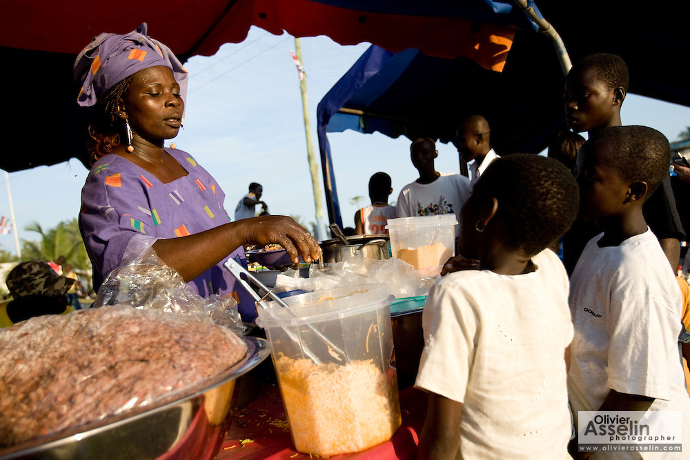 A woman serves customers at a small kiosk selling food during the annual Oguaa Fetu Afahye Festival in Cape Coast, Ghana on Saturday September 6, 2008.