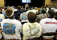 """Men wearing shirts with a pictures of fish on the back listen to a BP contractor lead a class in BP's """"Vessel of Opportunity"""" program for commercial fishermen and boat owners in Biloxi, Mississippi May 5, 2010.  The program trains boat operators in treating the oil spill still offshore. REUTERS/Rick Wilking (UNITED STATES)"""