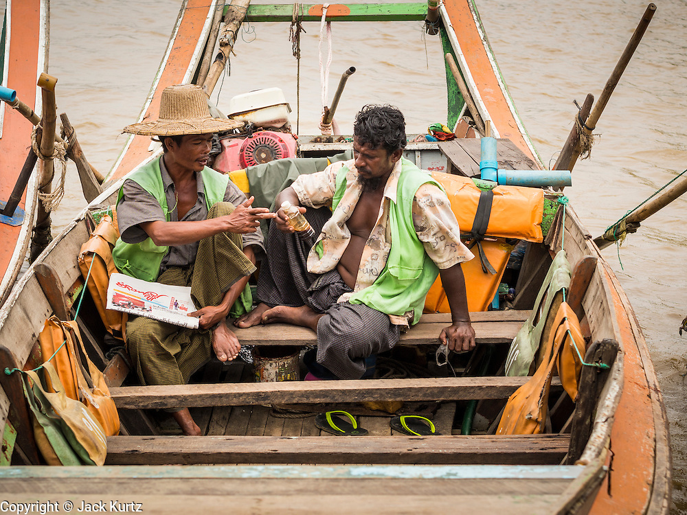 08 JUNE 2014 - YANGON, MYANMAR: Boatmen in their boats read a newspaper on the Yangon waterfront. Yangon, Myanmar (Rangoon, Burma). Yangon, with a population of over five million, continues to be the country's largest city and the most important commercial center.      PHOTO BY JACK KURTZ