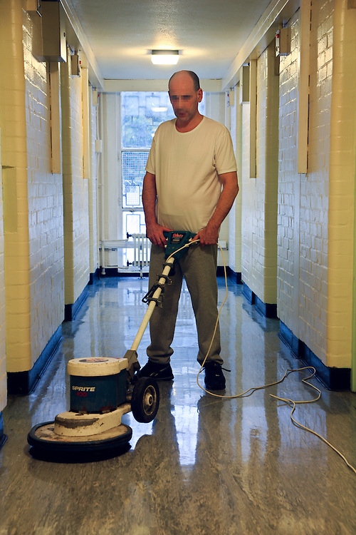A prisoner wing cleaner on the third level of C wing at Coldingley prison, he works all day polishing the floors..HMP Coldingley, Surrey was built in 1969 and is a Category C training prison. Coldingley is focused on the resettlement of prisoners and all prisoners must work a full working week within the prison. Its capacity is 390 prisoners.
