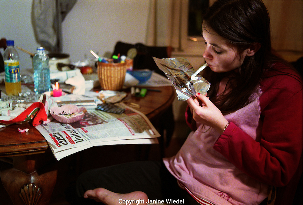 Young female addict smoking heroin at home.