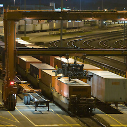 Late at night, an intermodal train has arrived from the west coast to BNSF Railway's intermodal terminal in Cicero, IL. The gantry crane is going to work unloading the inbound cargo.
