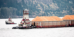 Two boats pass in the Columbia River Gorge, a large tug pushing barges of wood chips downstream and a smaller tug returning upstream without a load, Washington-Oregon, USA