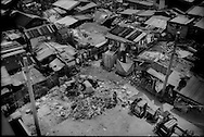 Looking down on Baseco Compound where young boys pick through refuse for recyclables.<br /> <br /> While the extreme poverty rate in the region dropped significantly between 2005 and 2008, the Philippines' poverty rate remained largely unchanged.  In fact, poverty has intensified on the poor.  According to the National Statistics Coordination Board (NSCB) in 2006, 28.8% of families lived on less than US$1.25/ day.  By 2012, 27.9 % of Filipinos were living below the poverty line.  <br /> <br /> What what changed was the income per family needed to escape extreme poverty.  While in 2006, a family would need to earn US$39.09 / month to escape extreme poverty, that figure rose in the most recent NSCB survey to US$ 181.89/month, clear showing how inflation is weighing heaviest upon that society's poor.