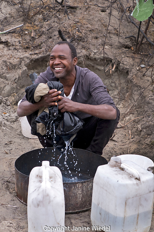 Refugee from Darfur Sudan washing his clothes in a bucket. The Calais Jungle Refugee and Migrant Camp in France
