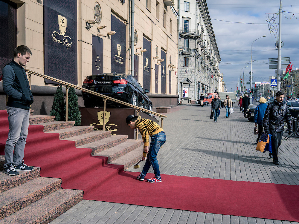 A man sweeps a red carpet outside a casino, of which there are many - mostly catering to wealthy Russians - on Friday, October 9, 2015 in Minsk, Belarus. President Alexander Lukashenko, a longtime iron-fisted ruler of Belarus, was elected to a fifth term with a reported 83.5% of the vote, which international monitors said did not meet democratic standards.