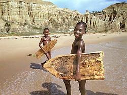 Angolan children attempt to surf on their hand made surf boards which they carved out of driftwood after they watched French foreigners surfing on the beaches outside of the capital of  Luanda  in this file photo.  President Jose Eduardo dos Santos, who has led Angola since 1979, said he would not run in presidential elections planned for next year.  Angola's brutal 26 year-civil has displaced around two million people - about a sixth of the population - and 200 die each day according to United Nations estimates. .(Photo by Ami Vitale)