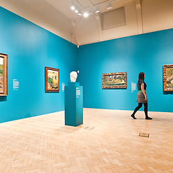 London, UK - 19 June 2013: Hannah Talbot, marketing managar at the Courtauld Gallery walks past canvases and a marble sculpture by post-impressionist painter Paul Gauguin at the Courtauld Gallery.