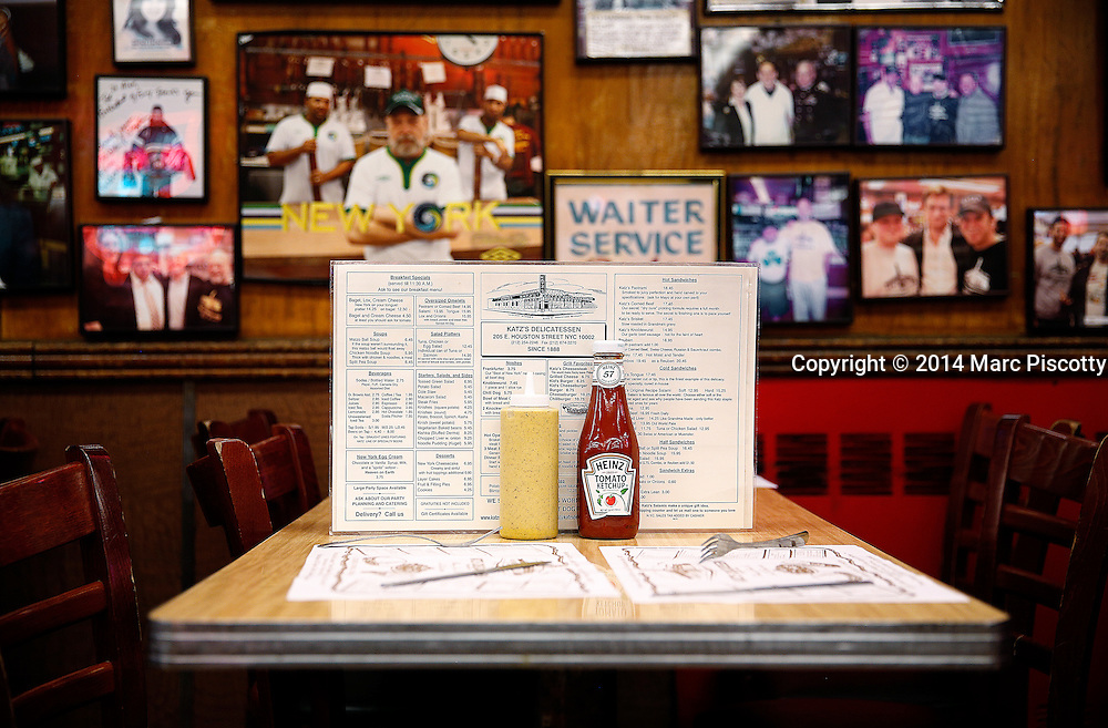 SHOT 5/6/14 10:24:40 AM - A menu along with ketchup and mustard on a table at Katz's Delicatessen in New York City. Also known as Katz's of New York City, is a kosher style delicatessen restaurant located at 205 Houston Street, on the southwest corner of Houston and Ludlow Streets on the Lower East Side in Manhattan, New York City. New York is the most populous city in the United States and the center of one of the most populous urban agglomerations in the world—the New York metropolitan area. The city is referred to as New York City or the City of New York to distinguish it from the State of New York, of which it is a part. A global power city, New York exerts a significant impact upon commerce, finance, media, art, fashion, research, technology, education, and entertainment. New York City has often been described as the cultural and financial capital of the world. (Photo by Marc Piscotty / © 2014)