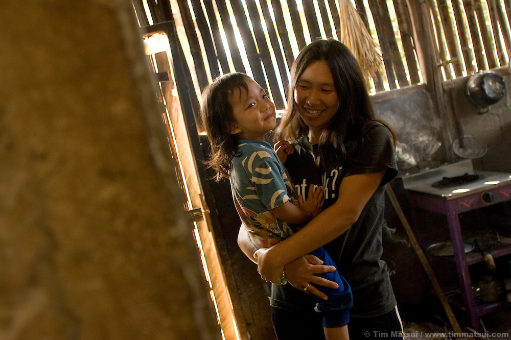 Ayee with her sister's four year-old son Nalin in the Akha hill tribe town of Senjai near Mae Sai, northern Thailand. Ayee was sold as a young girl to a German who took her to Germany; she returned months later to find her younger sister Booka living and studying at DEPDC where her risk of being trafficked like Ayee was minimized. Soon Ayee moved to the DEPDC facility where she learned how to cope with her experience; today as a woman in her mid-thirties she is an advocate for women's and children's rights works in her 50,000 person municipality to end human trafficking...DEPDC is addressing the issue of human trafficking in northern Thailand by providing a safe place to live and study for youth who are at risk of being trafficked..