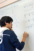 Seattle, Washington: April 9, 2010.  Community college student at a whiteboard ponders a math problem during an afterschool secondary school math class that promotes independent learning and peer tutoring.