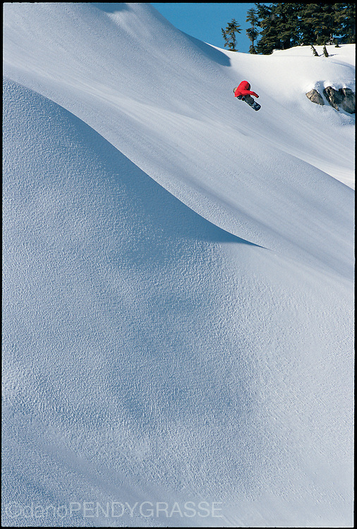Snowboarder Mike Page spins over a pristine snowscape near Whistler, BC.