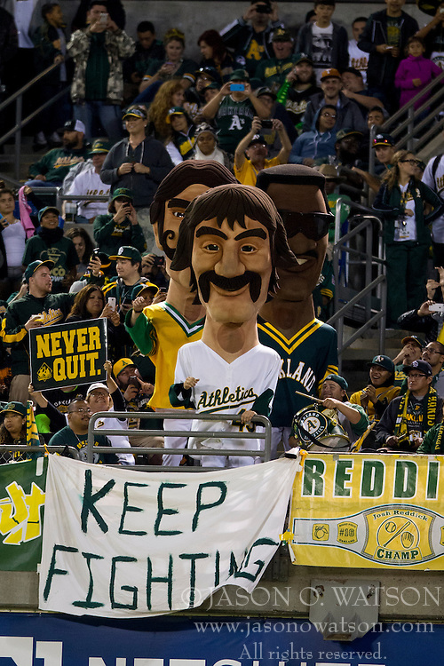 OAKLAND, CA - SEPTEMBER 23:  Oakland Athletics fans and hall of fame mascots hold up signs encouraging their team during the seventh inning against the Los Angeles Angels of Anaheim at O.co Coliseum on September 23, 2014 in Oakland, California. The Los Angeles Angels of Anaheim defeated the Oakland Athletics 2-0.  (Photo by Jason O. Watson/Getty Images) *** Local Caption ***