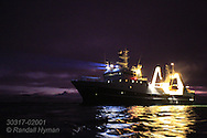 RV Helmer Hanssen glows amid winter darkness during polar night in January on a marine science expedition in Kongsfjorden, Svalbard, Norway.