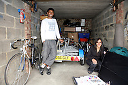 Moynul Ahmed, 32, courier, and his sister, Noorjehan Rashid, 19, on a gap year, in the family garage on an estate in East London. Objects : save for a carpet, their sister's architectural models for a university project and a few bikes.