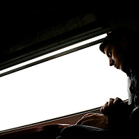 A man reads a book as he rides the express train to Marrakesh, from Casablanca, Morocco.