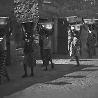 A group of girls carry millet loads in large vessels balanced on their heads, Tireli, Dogon country, Mali.