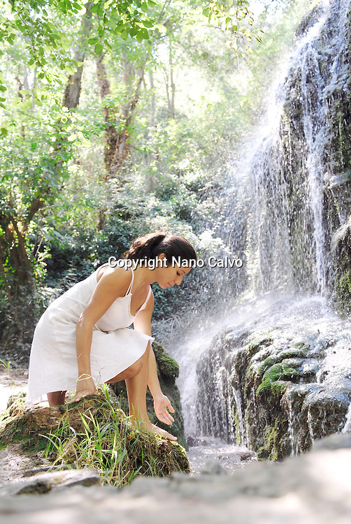 Beauty and Health Images by Nano Calvo - Model Released Young attractive brunette woman, wearing a white dress, touching the water in a beautiful natural place, with a waterfall and assorted vegetation