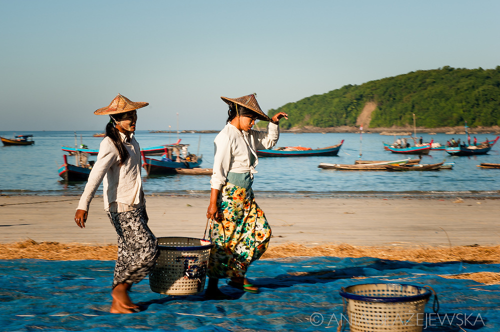 Myanmar, Ngapali. Two woman carry a big basket full of fish.<br />