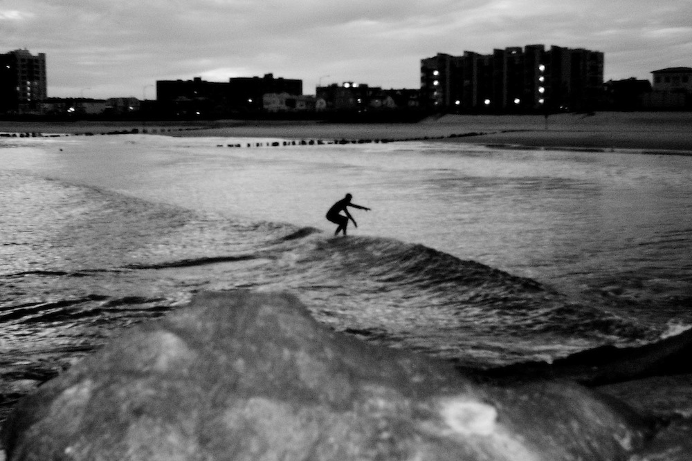 A surfer catches a wave at Rockaway Beach, Queens, NY.