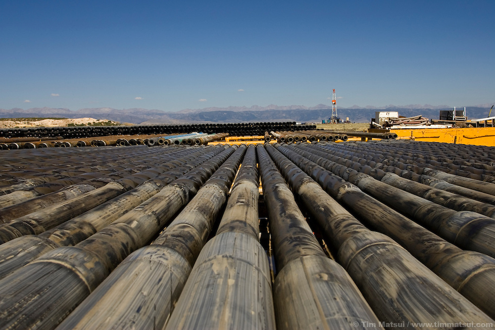 """PINEDALE, WY - Racks of drilling pipe for Caza drill rig 86 on the Pinedale Anticline near Pinedale, Wy., (pop. 1400) on August 18, 2005. """"We're doing our best to keep the Californians from freezing to death in the dark,"""" jokes company man Chris Holten, who has been an engineer in the petroleum industry for years. Questar, one of the main natural gas lease holders in Sublette County, which encompasses the Jonah Field, was recently granted approval for year-round drilling operations in the Pinedale Anticline, an environmentally sensitive winter forage ground for big game, part of the longest big game migration route in the lower 48, as well as hosting the largest remaining population of sage grouse. Some of the reasons for approval were Questar's proposal of fewer drill pads, more directional drilling, and a pipeline to transport condensate and water out of the environmentally sensitive areas. Critics say these changes should have been standard in the initial drilling permit which, were it to be followed, would have amounted to a greater overall environmental impact than the newly approved plan. Year-round drilling will allow the company to develop its wells in about half the time (10 years vs. 18 years) and to stabilize a seasonal influx of workers, allowing contracted employees to take up residence in the area instead of spending the summers in company man-camps or the area hotels. In the nearby Jonah Field where operators are seeking an 'in-fill' project with the number of cheaper straight-down wells increasing from 533 to 3100, Encana, one of the chief operators, is expected to drill two thirds of the wells to yield upwards of 10.5 trillion cubic feet of natural gas which has a current market value of $55 to $60 billion dollars. Encana could make $2 billion in profit per TCF depending price trends and production costs. Amongst Pinedale Anticline engineers there is already talk of in-fill projects and deep wells reaching down to 20,000 feet. Current wells are in t"""