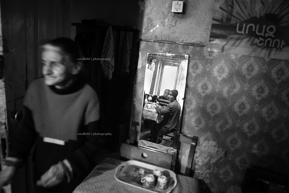 """Rusana enter her living room where she hosts some nighbours for lunch. This image is part of the photoproject """"The Twentieth Spring"""", a portrait of caucasian town Shushi 20 years after its so called """"Liberation"""" by armenian fighters. In its more than two centuries old history Shushi was ruled by different powers like armeniens, persians, russian or aseris. In 1991 a fierce battle for Karabakhs independence from Azerbaijan began. During the breakdown of Sowjet Union armenians didn´t want to stay within the Republic of Azerbaijan anymore. 1992 armenians manage to takeover """"ancient armenian Shushi"""" and pushed out remained aseris forces which had operate a rocket base there. Since then Shushi became an """"armenian town"""" again. Today, 20 yeras after statement of Karabakhs independence Shushi tries to find it´s opportunities for it´s future. The less populated town is still affected by devastation and ruins by it´s violent history. Life is mostly a daily struggle for the inhabitants to get expenses covered, caused by a lack of jobs and almost no perspective for a sustainable economic development. Shushi depends on donations by diaspora armenians. On the other hand those donations have made it possible to rebuild a cultural centre, recover new asphalt roads and other infrastructure. 20 years after Shushis fall into armenian hands Babies get born and people won´t never be under aseris rule again. The bloody early 1990´s civil war has moved into the trenches of the frontline 20 kilometer away from Shushi where it stuck since 1994. The karabakh conflict is still not solved and could turn to an open war every day. Nonetheless life goes on on the south caucasian rocky tip above mountainious region of Karabakh where Shushi enthrones ever since centuries."""